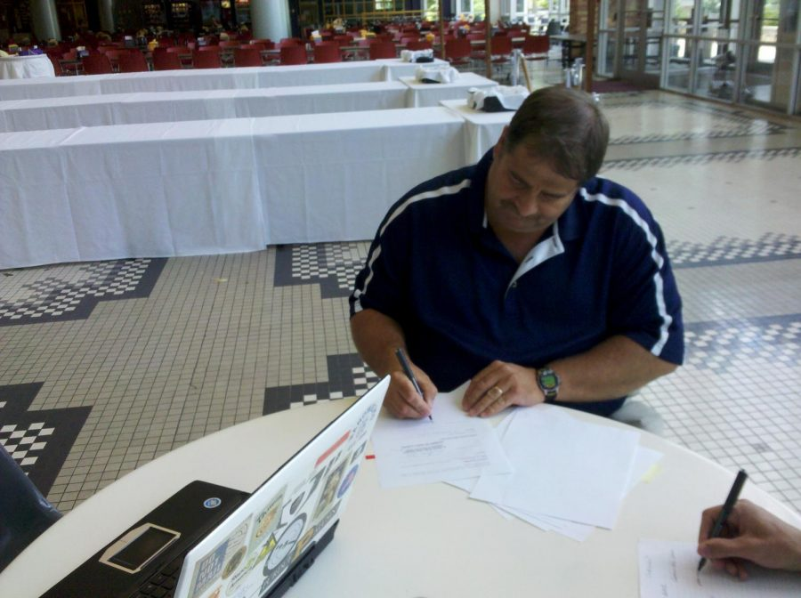 An official at UNA signs a contract in the Guillot University Center to bring in a film rental kiosk to the GUC this fall.