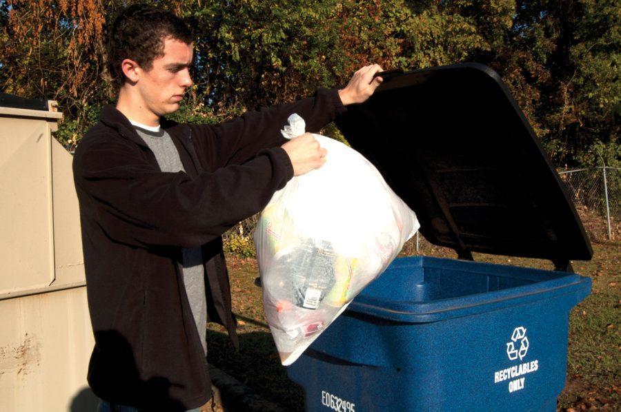 UNA student Ben Mills recycles reusable materials near campus.