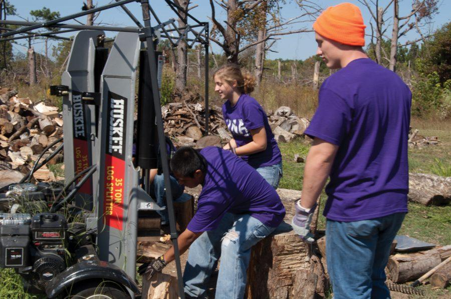 (From front to back) UNA students Payton Edmiston, Bert Pena and Katelyn Jarrell of Alternative Break Board help chop wood from damaged trees from the April tornadoes during fall break in Harvest Oct. 8.
