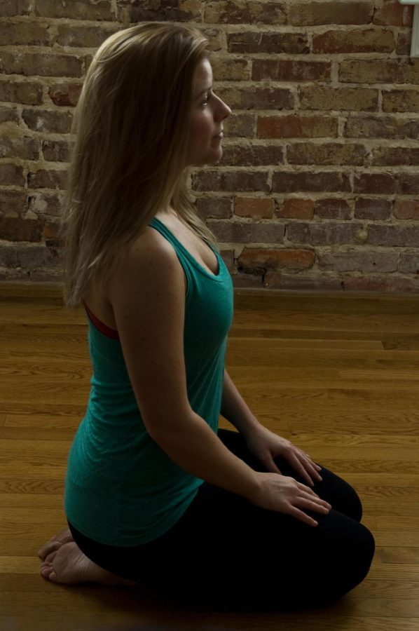 Danielle Snoddy, founder and owner of Shoals Yoga, sits in the Virasana, or the Hero, pose.