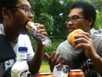 Tren Chao (left) and Zhizheng Zhehg eat sandwiches outside. International students often view hamburgers and pizza as stereotypical American foods.