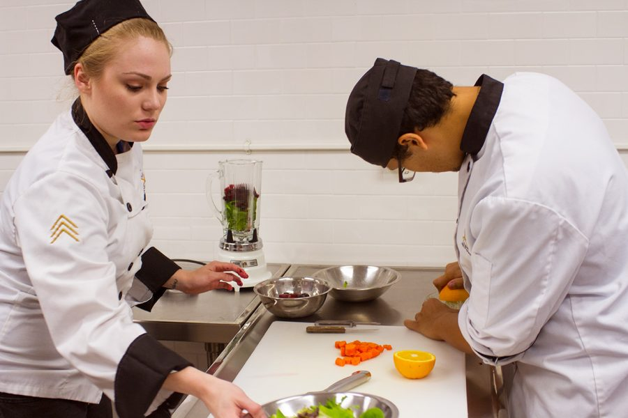 Culinary+Arts+students+Ana+Albyn+and+Christopher+Mercado+work+together+to+prepare+a+meal+for+their+classwork.%0A