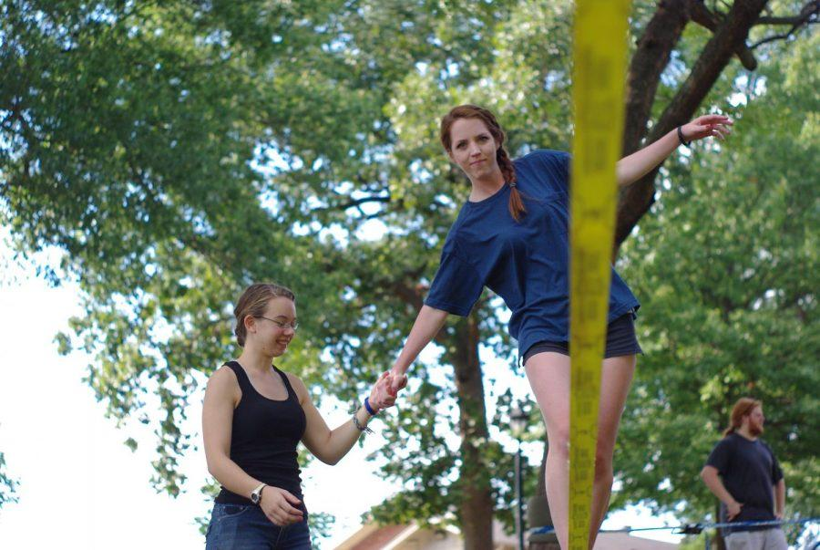 UNA+student+Sarah+Beth+Simpson+helps+fellow+student+Jessica+Colyer+across+a+slackline+at+an+Outdoor+Club+event+held+on+campus+Sept.+18.%0A