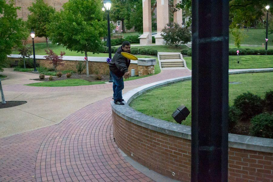 A+UNA+student+plays+frisbee+golf+on+campus%2C+aiming+for+a+light+pole+near+Willingham+Hall.%0A