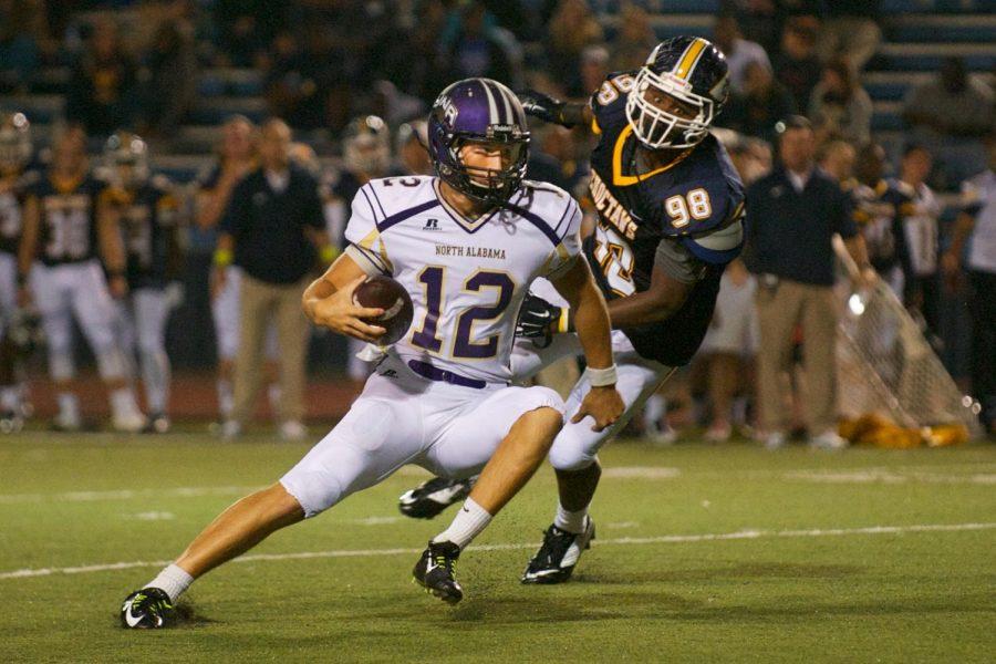 Quarterback Luke Wingo fights off a Mississippi College defender Sept. 13