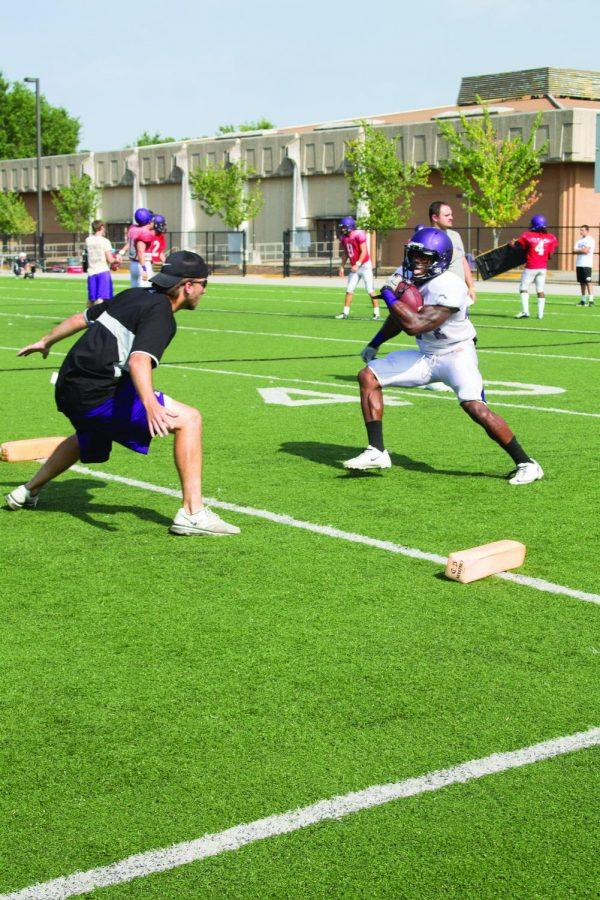 Running back Lamonte Thompson darts around one of his coaches during practice Aug. 26.