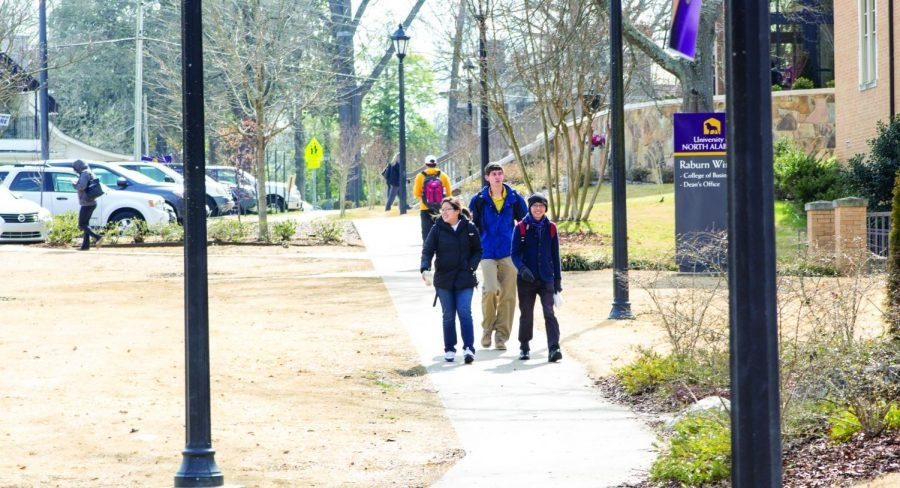 Three+students+walk+across+campus+Feb.+23+outside+Keller+Hall.+University+research+shows+the+student+population+is+more+diverse+than+the+faculty+and+administration.