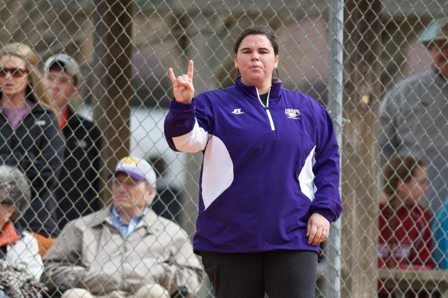 Head+softball+coach+Ashley+Cozart+signals+there+are+two+outs+to+her+players+in+game+against+Maryville+University+Feb.+8.+Cozart+is+in+her+second+season+at+UNA+and+has+led+the+Lions+to+a+top+25+ranking+this+season.