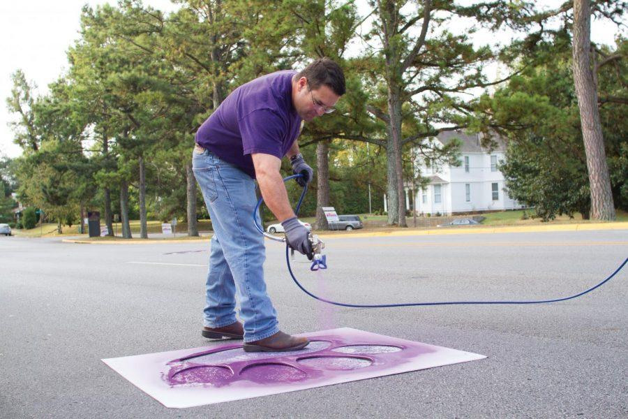 University+painter+Keith+Fields+sprays+purple+paint+over+a+paw+print+stencil+on+Pine+Street+Sept.+27.+After+the+paint+was+sprayed+on+the+stencils%2C+volunteer+students+outlined+the+purple+paw+prints+with+pearl+white+paint.