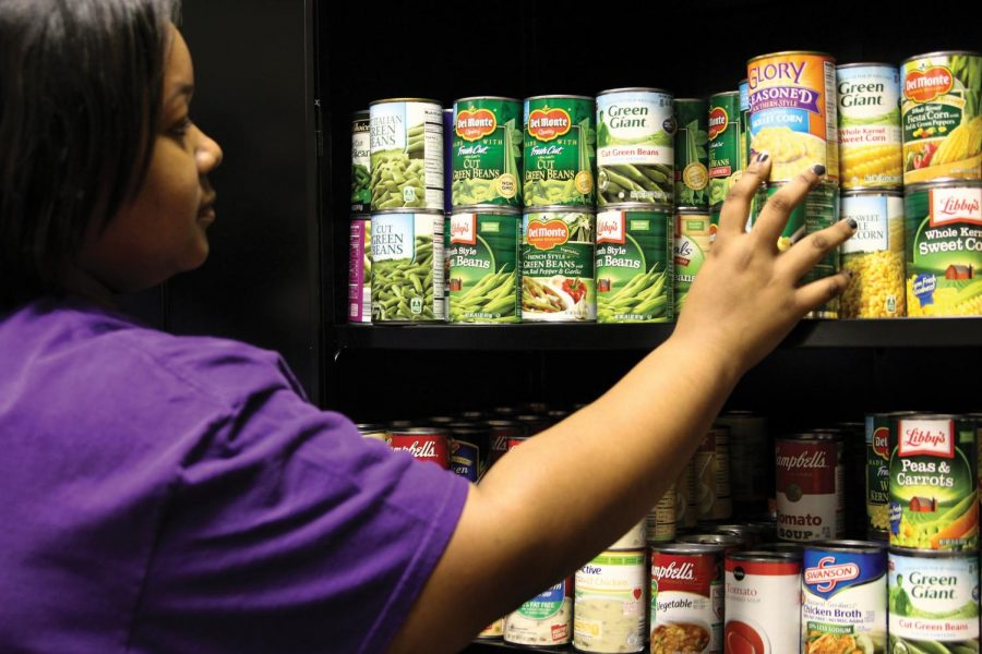 Pantry Coordinator Justiss Martin fills the Feeding the Pride pantry shelves with donated canned goods. The food pantry, located in GUC 225,  is a service provided to all UNA students free of charge.