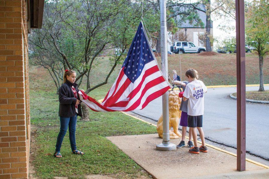 Kilby School students Riley Webb (left), Colton Persell and William Watson raise both the American and Alabama state flags. There are certain rules how the flag is displayed, said ROTC Recruiting Operations Officer Jose Atencio.