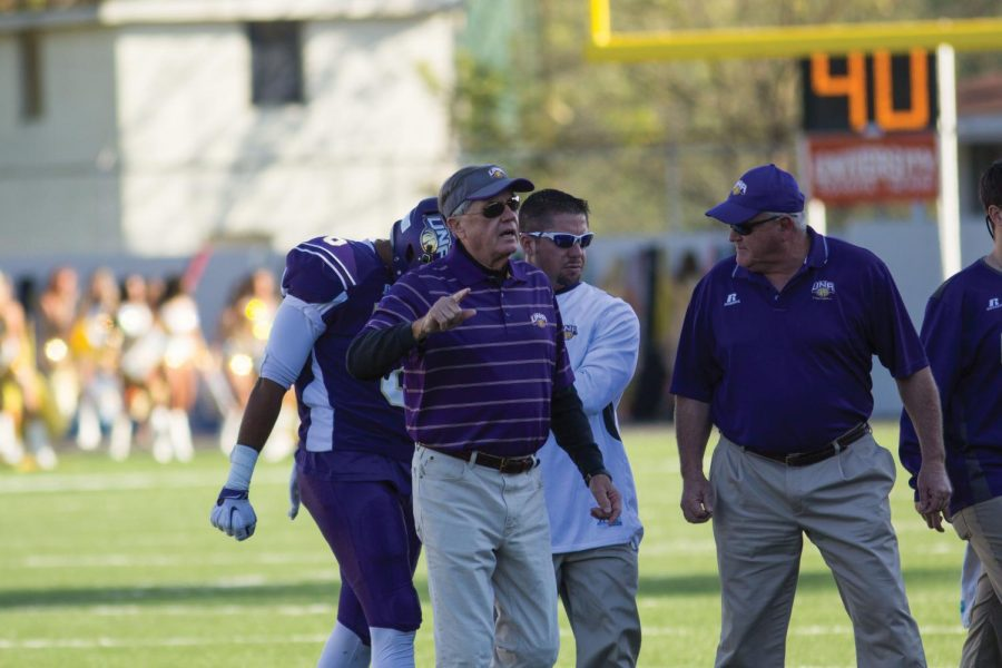Former UNA head athletic trainer Johnny Long (middle) assists current head trainer Josh Penny (white), as they help defensive back Jalen Reedus off the field after an injury. Long still has a hand in helping athletes treat injuries, as well as teaching classes as a professor.