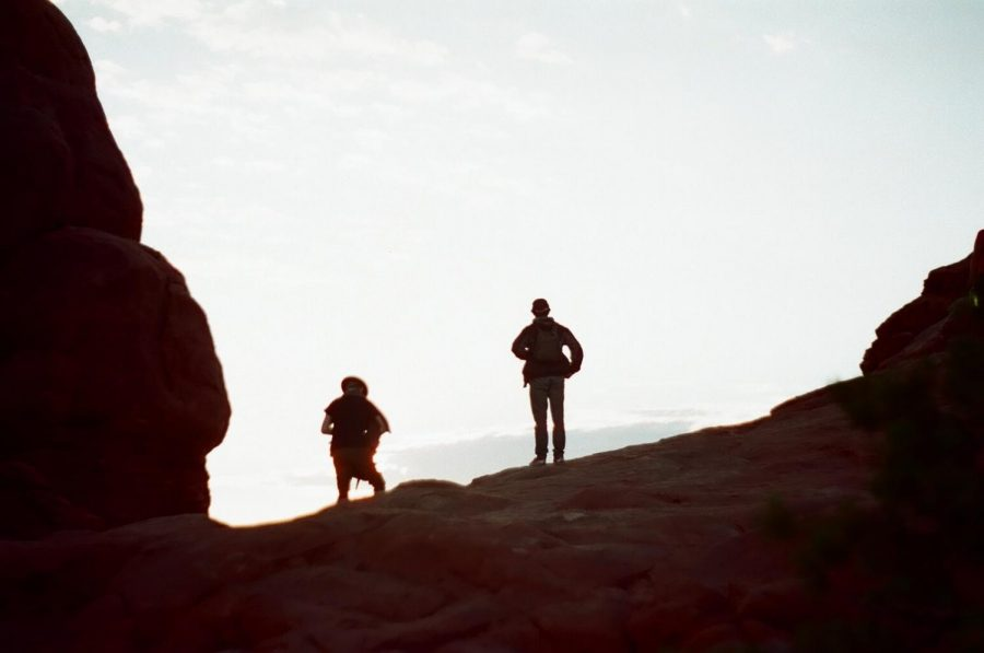 """Senior Tate Hipps (left) and Justin Argo near the end of their cross-country journey at Arches National Park in Moab, Utah. Hipps films the landscape just as the sun rises. Hipps spent 18 months working on his documentary, """"Koinonia with God,"""" which took him across the country and to Guatemala."""
