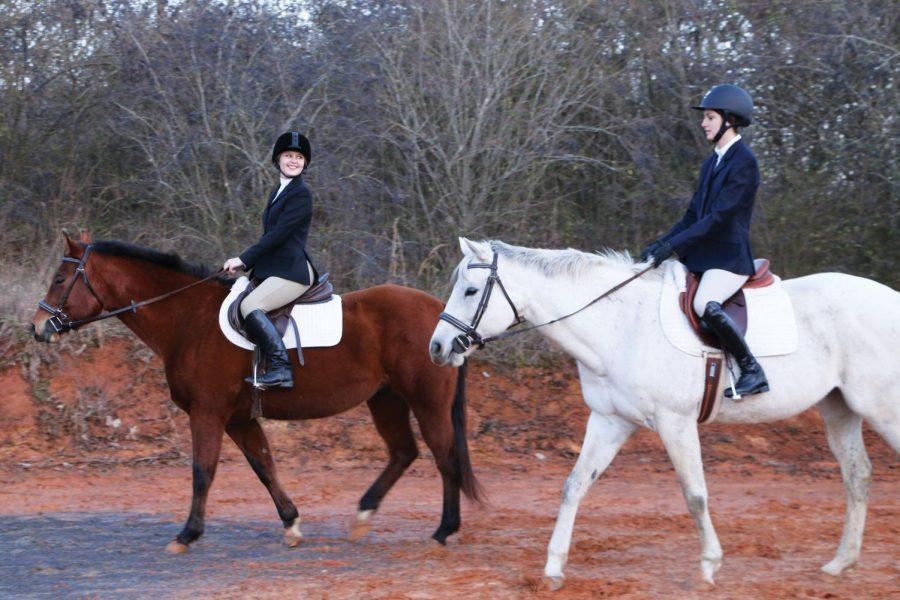 First+year+graduate+student+Elizabeth+Tyson+%28left%29+and+junior+Whitney+Pacil+ride+their+horses+side+by+side+Jan.+24.+Both+girls+are+founding+members+for+the+UNA+equestrian+team.