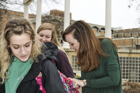 SGA President-elect Sarah Green pins a button on Rachel Hutto