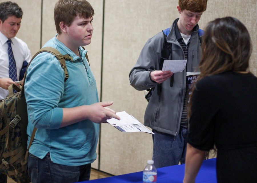 Students complete their National Rife Association membership cards while talking NRA Grassroots Coordinator Natasha Montague. Students could become members of the NRA for free at the event.