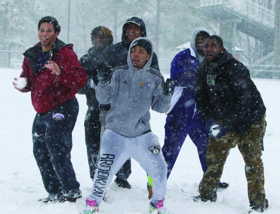 Students have a snowball fight as snow continues to fall on campus in February 2015. Officials recently closed campus for potential winter weather, but little precipitation fell.