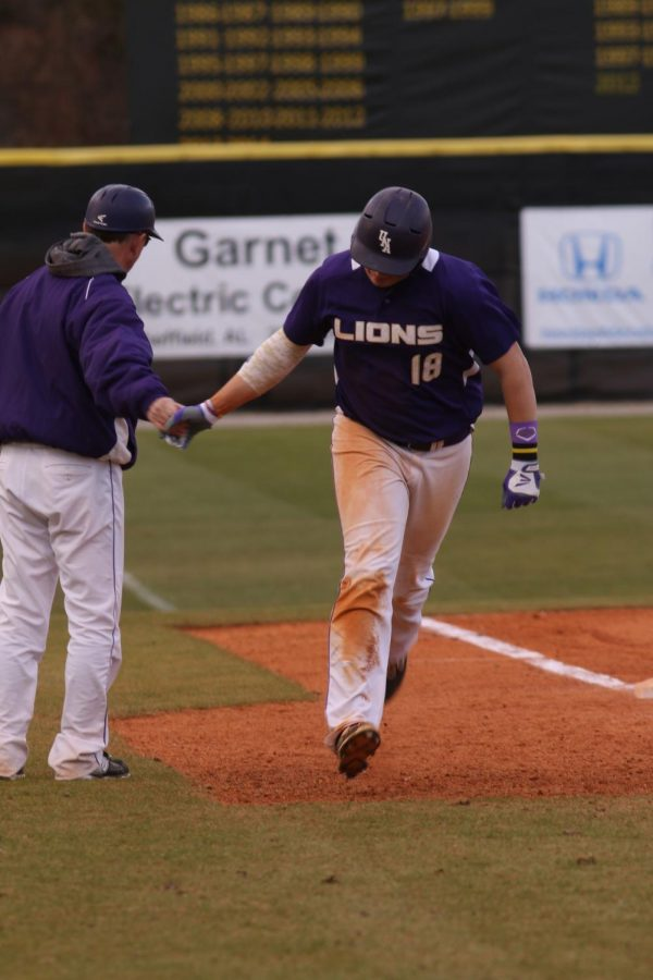 Sophomore+first+baseman+Kyle+Hubbach+rounds+third+and+high+fives+head+coach+Mike+Keehn+after+hitting+a+home+run+against+Stillman+Feb.+7.+The+Lions+%2819-17%2C+11-13+Gulf+South+Conference%29+snapped+a+nine+game+losing+skid+by+defeating+Spring+Hill+College%2C+then+sweeping+Mississippi+College+April+9-10.