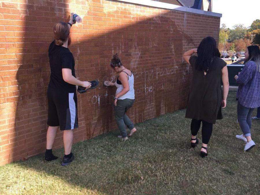 Students+work+to+clean+chalk+graffiti+off+the+Commons+Oct.+31.