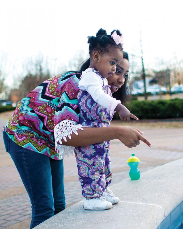 Senior Marissa Phillips and her daughter, Makynlee Blair, look into the fountain at Harrison Plaza.