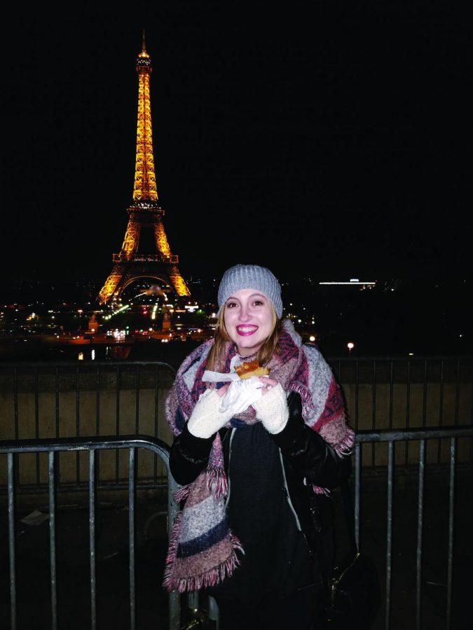 Alumna Alexandria Buttgereit eats a slice of pizza in front of the Eiffel Tower. The Magellan Exchange program allowed her to visit Paris.