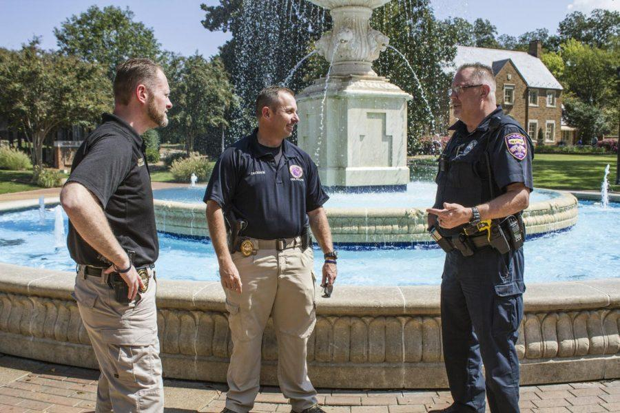 (From L to R) UNA Chief of Police Kevin Gillilan, Captain Les Jackson and Officer McGee take a break from duties to talk in front of Harrison Fountain. The UNA Police Department, located in the basement of Keller Hall, keeps watch over campus to make sure faculty/staff and students stay safe.