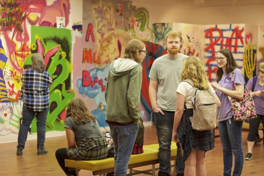 Students+observe+the+art+at+the+UNA+Art+Department%27s+%22A+Voice+for+All%22+graffiti+exhibit.+Featuring+works+from+art+students%2C+faculty+and+alumni%2C+the+collection+of+designs+covers+the+walls+of+an+entire+upstairs+room+in+the+University+Art+Gallery.