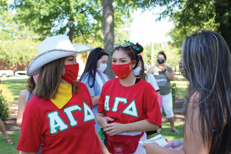 Sisters+of+Alpha+Gamma+Delta+welcome+a+new+member+after+she+opened+her+bid.+This+year+the+campus+tradition+was+a+private+event+held+across+campus+instead+of+at+Memorial+Amphitheater.+Masks+and+social+distancing+were+required.