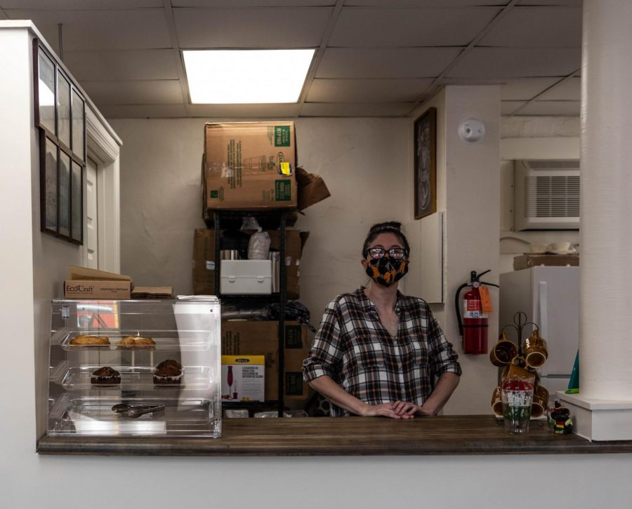 Owner+Kristin+O%E2%80%99Kain+smiles+proudly+%28underneath+her+mask%29+behind+the+counter+of+her+coffee+shop.