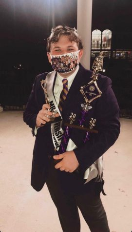 "Gordon smiles as he accepts his awards of ""Mr. University"" and ""Mr. Phi Mu."" He wears a mask featuring many of his best moments at UNA, including SOAR, LaGrange and SGA."